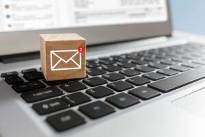 Laptop auf dem ein Baustein mit E-Mail-Symbol steht